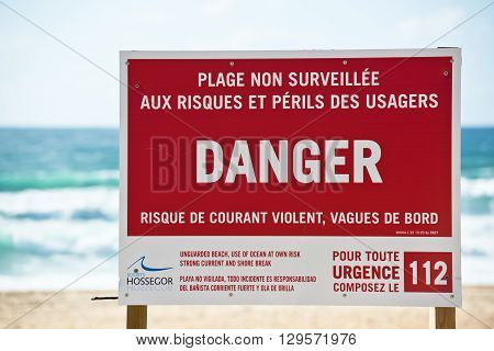 FRANCE ONDRES - SEPTEMBER 18: Red danger sign on an ocean beach with waves on the background on September 18 2015