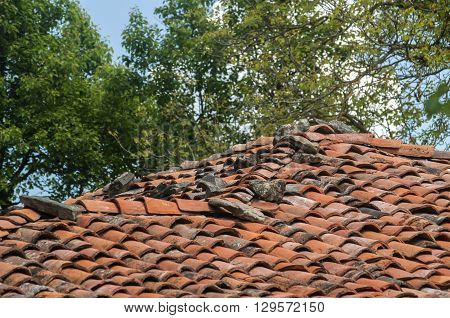 Roof of rural country house covered with old clay tiles