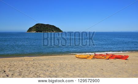 Scene in the Abel Tasman National Park New Zealand. Ocean island and kayaks at the beach.