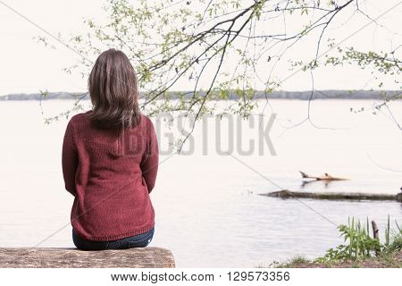backside of brunette young woman sitting on tree in front of a lake