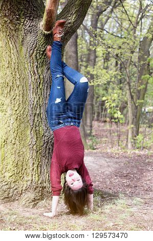 brunette woman making a headstand at a tree and pulling out her tongue