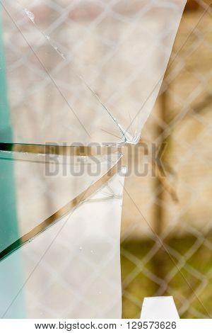 Sharp glass hole cracks splinters broken glass by the street.