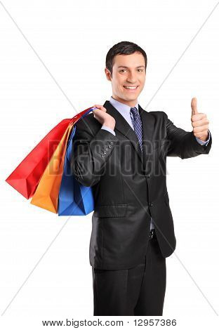 A Happy Male Holding Shopping Bags And Giving Thumb Up