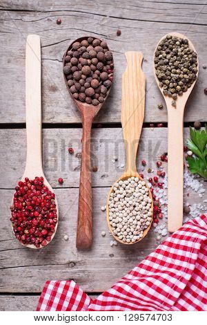 Seasoning for cooking. Red white and allspice pepper and sea salt in wooden spoon on aged wooden background. Food ingredient. Selective focus. Flat lay. Top view.