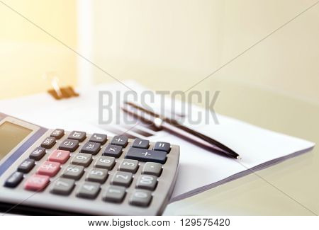 Soft focus of a pen and calculator with paperwork on the glass table; soft focus filter background for business concept.
