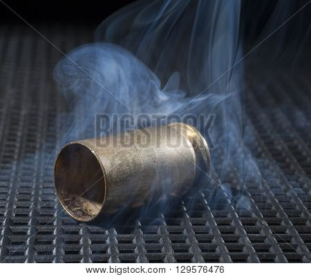 Semi automatic handgun brass on a black grate with smoke