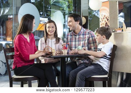 Family In Casuals Having Ice Creams In Parlor