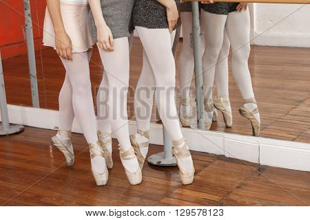 Low Section Of Ballerinas Performing Pointe On Floor