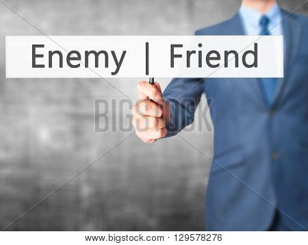 Enemy  Friend - Businessman Hand Holding Sign