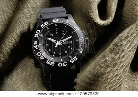 Tritium military watch on camouflage cloth, close up