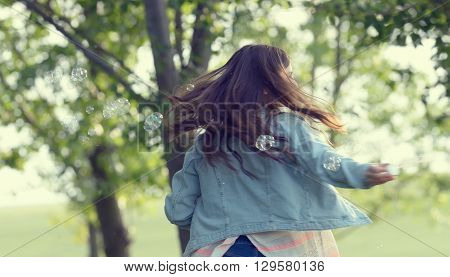Young girl play with soap-bubbles in forest