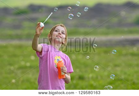 little girl play with soap bubbles on field