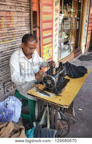 JAIPUR INDIA - NOVEMBER 13 2015: Tailor working in the street. A man works with his sewing machine on the sidewalk in Jaipur.