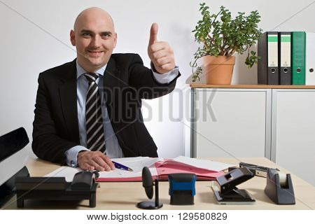 Successful manager holds up thumb. He is smiling.