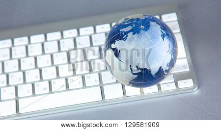 Cristal globe of the Earth on a Computer.
