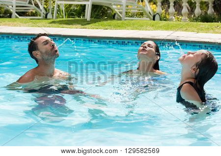 Happy family spitting water out from their mouth in a swimming pool. Family enjoying vacation and summer in a pool. Happy parents and daughter having fun in swimming pool.