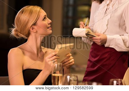 Young woman ordering food in a luxury restaurant. Woman confirming order holding menu card. Young beautiful woman listening to waitress while closing menu card.