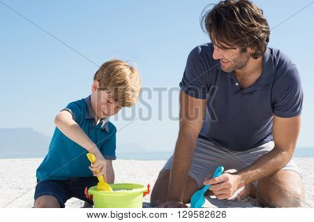 Cute little boy playing with sand at beach. Smiling father and son making sand castles in a summer day. Happy boy filling basket with sand.