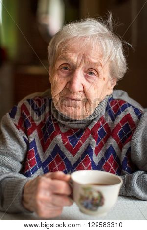 Old woman drinking tea.