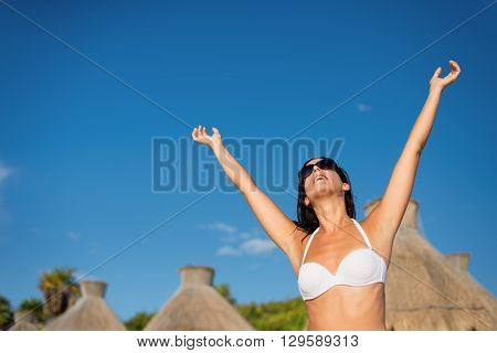 Blissful woman at tropical resort caribbean beach enjoying freedom and summer leisure. Summertime vacation tourism and travel concept. Brunette sunbathing and relaxing at Mayan Riviera Mexico.
