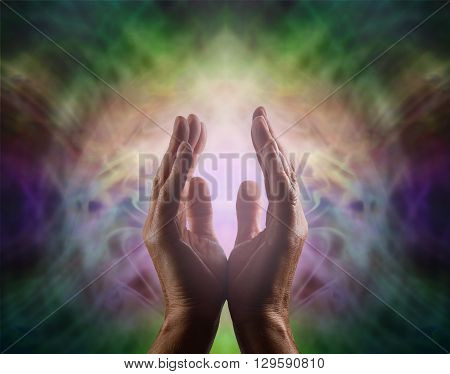 Pranic healer with beautiful Aura -  Complex multicolored vignette energy field with male hands reaching up and a gentle pink light between