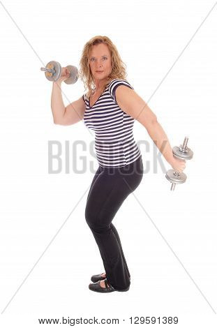 A strong middle age woman in black pants and striped top working out with two dumbbells isolated for white background.