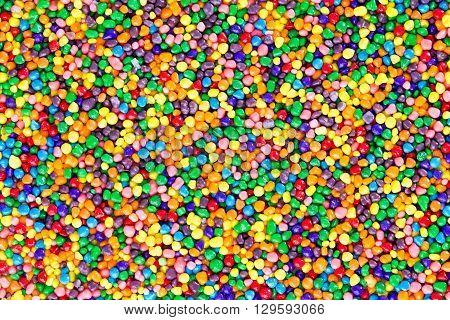 Background texture of colorful sugar candy pearls in the colors of the rainbow viewed overhead in a layer full frame