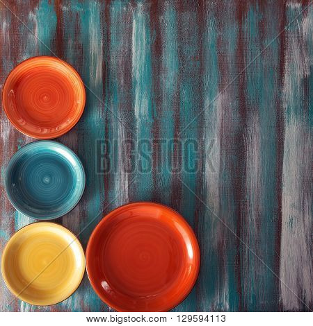 Colored plates in the corner of the old wooden background. Top view.