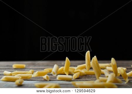 Falling penne pasta. Flying yellow raw macaroni over black background.