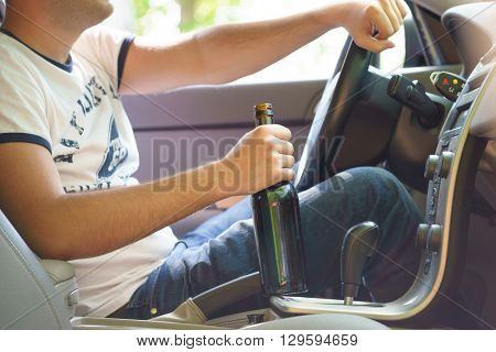 Man drinking beer while driving the car.