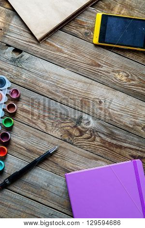 Watercolors, color pencils and sketchbook on wooden table. Flat lay photo with empty space for logo, text.