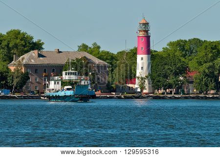 Baltiysk, Russia - June 29, 2010: Nida ferry boat on Baltic Spit for cars and people over old lighthouse background. ex-Pillau. Kaliningrad region
