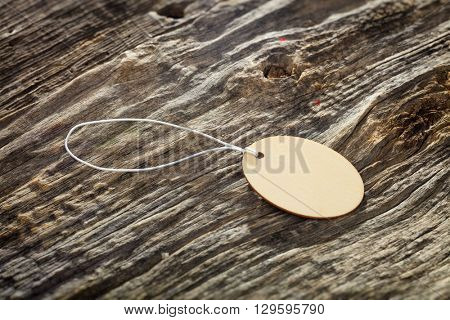 Oval tag made of wood with white rope on wooden background