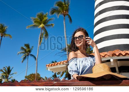 Beach vacation. A beautiful woman sitting on a sea-front on a blue sky and palms background.