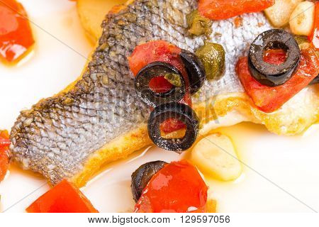 Fillet of seabass on a baked potato with capers and tomatoes. Macro. Photo can be used as a whole background.