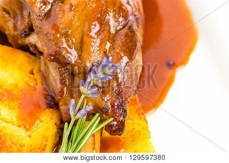 Fried lamb shank with polenta and covered with red sauce. Macro. Photo can be used as a whole background.