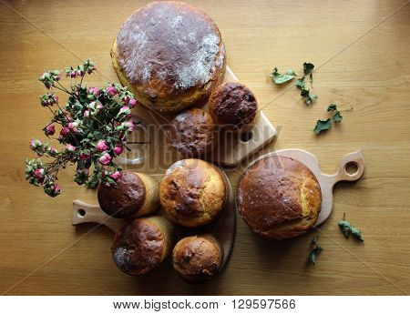 Homemade Easter bread loafs set background. Homemade sweet bread loafs upper view. Bread loafs on the table with dry roses bouquet.