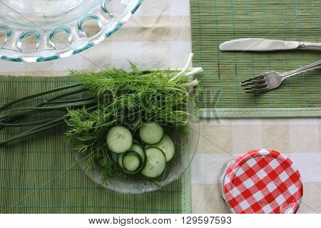 Greenery table set up. Green vegetables set on table with green table pads, cutlery and glass bowl. Red checkered  jar closure contrasting green table set.
