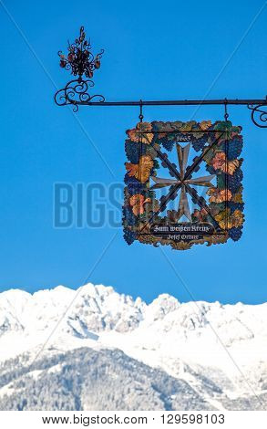 Innsbruck Austria - February 8 2010: A wine shop sign in Friedrich Strasse with the snowy mountains in the background