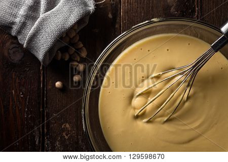 Chickpea Batter in a Bowl with a Whisk on Wood