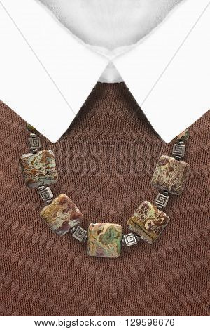 Ethnic necklace on brown pullover with white collar closeup
