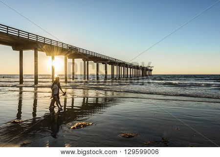 San Diego, USA - November 7, 2015: Couple walking by Scripps Pier during sunset in La Jolla, San Diego, California
