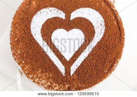 Tiramisu dessert with heart shaped pattern from powdered sugar and garnished with chocolate. Macro. Photo can be used as a whole background.