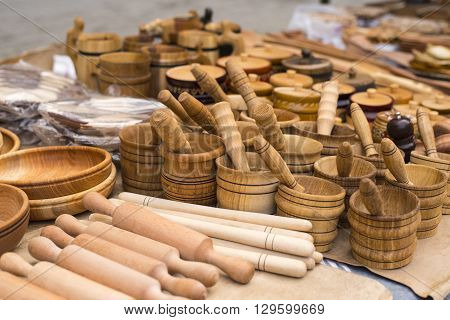 Handmade wooden vintage kitchen utensils for sale at the market. Various wooden kitchen tools. Different wooden tableware.