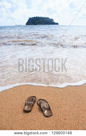 sandals on sand beach in summer sea in vacation and relax time