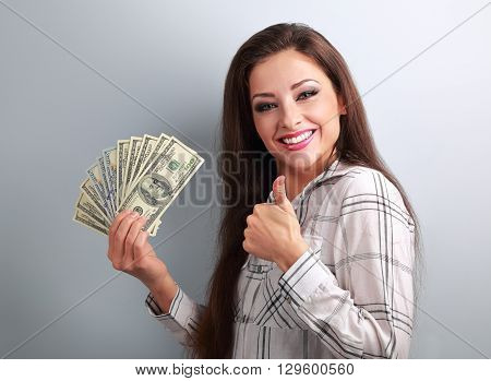 Young Happy Woman Holding Dollars And Showing Thumb Up Sign On Blue Background