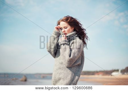 Attractive woman wearing a warm cardigan at the cold beach. Stock image.