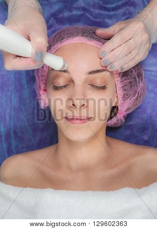 Closeup lovely happy young woman with hands holding medical maniples touching her face in Beauty salon. Cosmetician makes the procedure before applying the mask. Beautician cleanses the skin