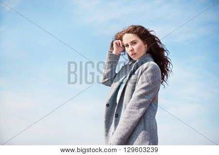 Young woman on the beach during a windy day. Stock image.