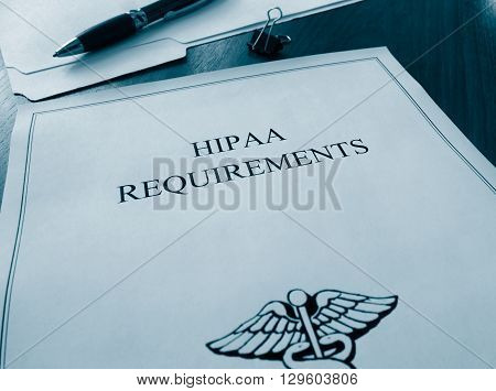 HIPAA requirements paper file on a desk
